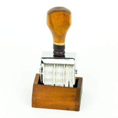 Classic vintage adjustable date stamp made by Oh, Hello Friend. It has a wooden handle and comes with a wooden base to rest in while not in use.